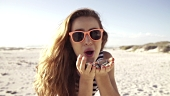 Young Woman blowing colorful confetti at the beach in slow motion