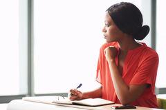 femme-d-affaires-africaine-faisant-une-pause-de-sa-session-intensive-d-écriture-87255097