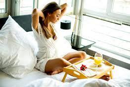 Femme prenat son petit-déjeuner au lit